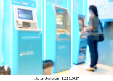 Blur image of woman stand at ATM machine, use for background.