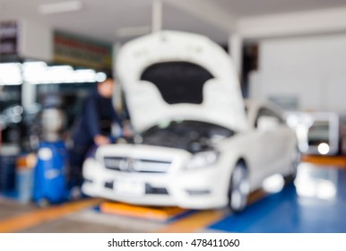 Blur image of worker fixing car in the garage for background usage.