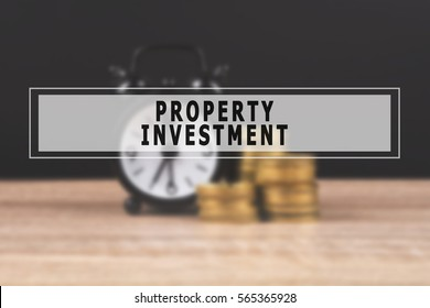 Blur images of alarm clock and money coin stack on wooden table and black background with text Property Investment. Finance concept, copy space.