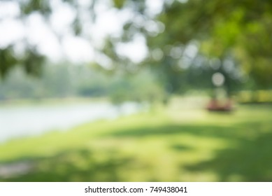 Blur of lake in city park bokeh background in summer, green nature concept