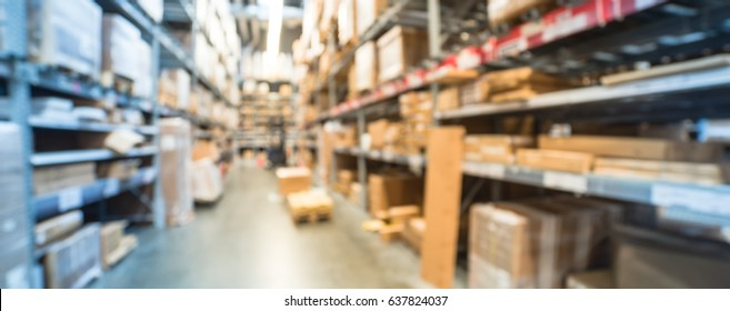 Blur large furniture warehouse in America, row of aisles, bins, shelves from floor to ceiling. Defocused industrial storehouse interior full of boxes. Inventory, wholesale, logistic, export. Panorama.