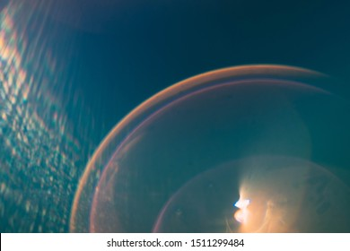 Blur lens flare. Teal blue abstract art background. Rainbow circles and light rays effect.