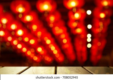 blur light of Chinese red lamp hanging at night with black wood table background in new year Asia festival celebration