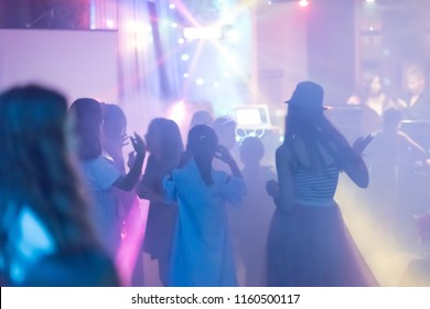 blur Light in club party Show And Silhouette hands of audience crowd people use smart phones enjoying the club party with concert. Blurry night club DJ party people enjoy of music dancing sound.