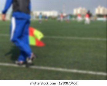Blur Lineman with the flag at the football match. Concept of sport. Lineman wear blue shirt suit hold the flag at the corner in football game.