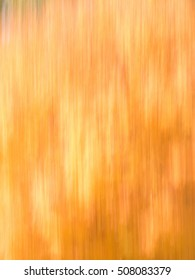 Blur of natural leaf colors in the Fall, specifically, oranges and yellows.  Suitable for background or abstract.