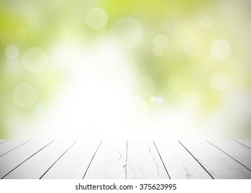 The blur nature greenery bokeh leaf wallpaper with white wood floor foreground on spring autumn park background. soft focus light view leaves flare;rays abstract tree foliage forest landscape gradient