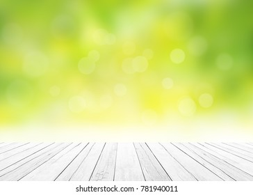 The blur nature greenery bokeh leaf wallpaper with white wood floor foreground on spring autumn park background. Soft focus light view leaves flare.