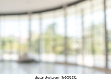 Blur office background empty white room lobby hall toward glass wall window interior view with light bokeh