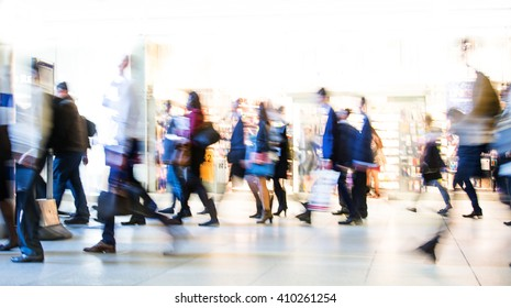 Blur of office workers walking pass the Canary Wharf tube station in early morning rush hours