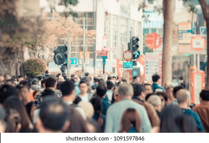 Blur out of focus. Anonymous people crowd walking on the downtown street of big city in Asia. City life concept