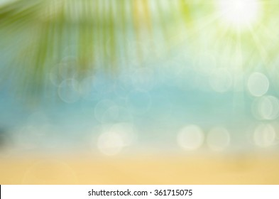 Blur palm leaf on tropical beach with bokeh sun light wave abstract background.Travel concept.