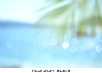 Blur palm leaf on tropical bokeh wave beach abstract background.Travel concept.