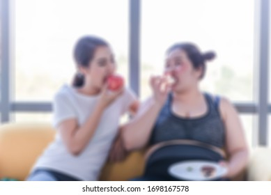 Blur patient women enjoy eating food on sofa