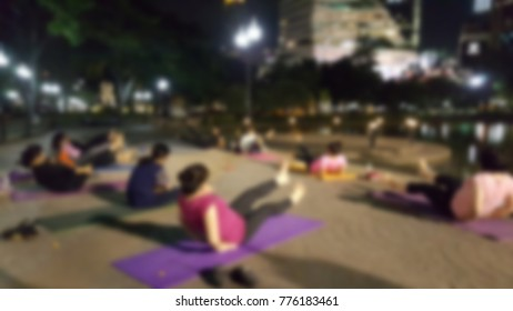 Blur of people doing yoga in small private group yoga class after working day at outdoor of public park, Thailand. City worker lifestyle after workday concept.
