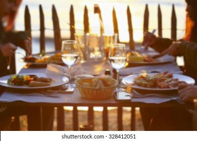 Blur of people having dinner on beach restaurant during summer sunset