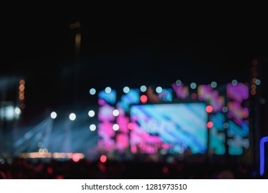 Blur people taking smart phone in night outdoor concert with colorful bokeh abstract background. Activity and lifestyle concept. Vintage tone filter color style.