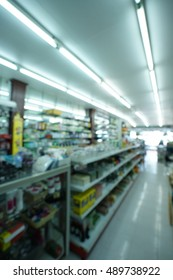 Blur pharmacy store with shelves of many medicines and indoor lights.