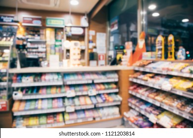 blur photo background of snacks and consumer product colorful in supermarket shop front shelf at counter cashier's desk. Mini-mart convenience stores are a new alternative for the urban people concept