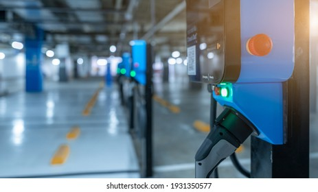 Blur photo of electric car charging station for charge EV battery. Plug for vehicle with electric engine. EV charger. Clean energy. Charging point at car parking lot. Future transport technology.