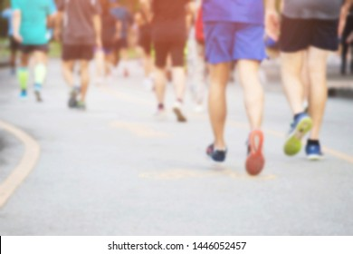 blur photo group of people crowd. Athlete runner feet running exercise on race track on the street road close up on shore in park public . fitness jog workout wellness concept.