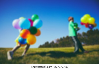 Blur photo of Happy boy and girl with balloons running together
