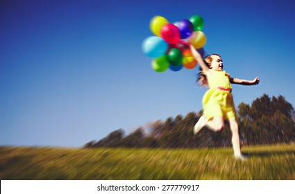 Blur photo of Little girl running with balloons on field