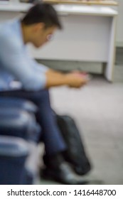blur photo of men who are sitting on the phone.