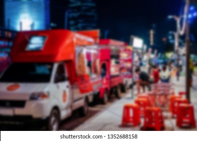 blur photo of Thai and travel People joined foodtrucks event that parking on the road beside footpath wait for customer to to buy food and drink. Bangkok Thailand.