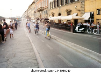 Blur photo of tourists walking, sightseeing, and biking on Florence street along side of Arno River, in the historical Old Town of Florence, Tuscany, Italy.
