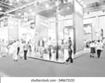blur photo of visitors at motor show in black and white filter