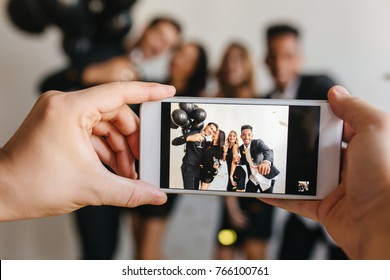 Blur portrait of blissful young people posing with balloons at birthday party with hands holding phone on foreground. Man taking photo of friends celebrating something and using smartpone.