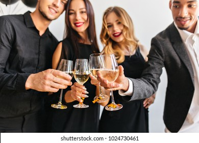 Blur portrait of cute curly woman and her friends with wineglasses on foreground. Fair-haired european female model celebrating new year with colleagues in office.