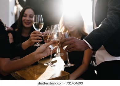 Blur portrait of smiling girls drinking wine in sunny day and talking around. Photo of relaxed women with male hands holding glasses full of champagne on foreground.
