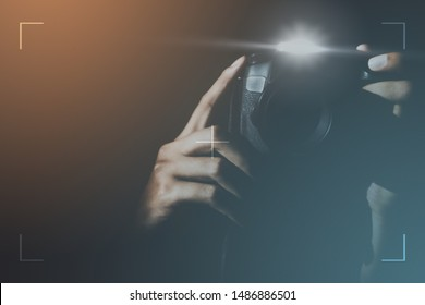 Blur of Professional photographers holding cameras and flash taking a photo with background look mysterious for photography or undercover agents. Detective or secretly taking pictures and stalking.