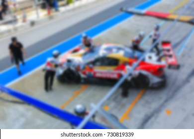 Blur professional pit crew ready for action as their team's race car arrives in the pit lane, concept of ultimate teamwork.