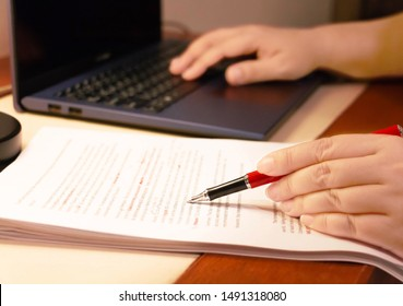 blur proofreading paper and computer laptop on table under lamp light