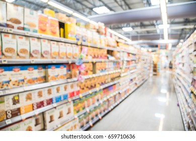 Blur selection of alternative milks, chocolate & bulk candies, jam, nut butter, hot, cold cereal on shelves in store at Houston, Texas, US. Defocused of aisles, row, variety product. Customer shopping