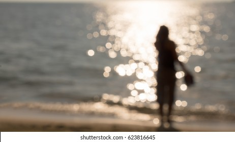 Blur shot of women with sandal on right hand side, bokeh sea and sunset background