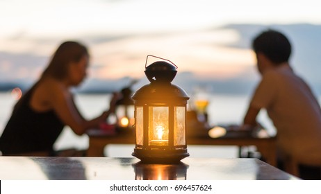 Blur silhouette loving couple under romantic candle light dinner and lantern with sunset twilight sky and summer seascape at restaurant or bar on beach front for valentine's background