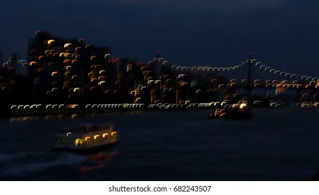 Blur slow motion of Ed Koch Bridge over East River and small boat at twilight