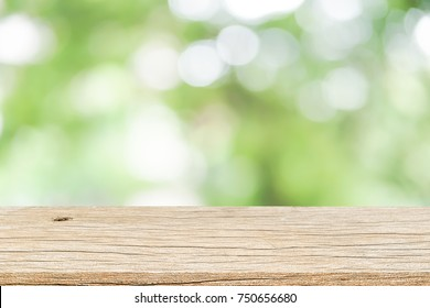 blur soft green color organic nature background with glow sunny light and aged plain wood table top perspective view for promote product concept.