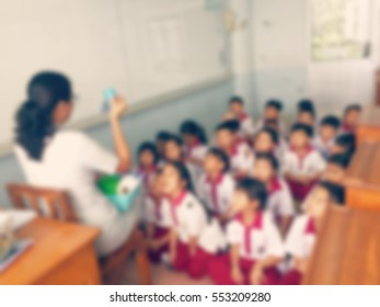 Blur students and teacher in the classroom for background usage.