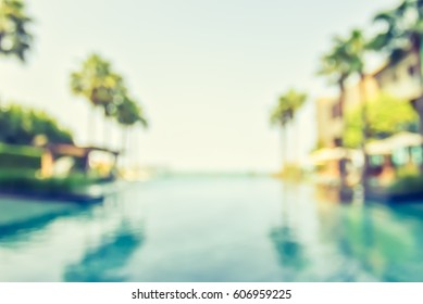 Blur summer background for resort hotel relaxation swimming pool party with blue cool sky and tropical palm tree