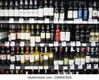 Blur supermarket sale liquor, Wine, Whisky or Alcohol drink section on shelve background, Many Alcohol drink bottles sale on the shelf in supermarket, as blurred effect background, Alcohol section.