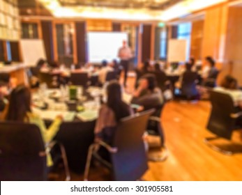 Blur of Training Course in The Big Conference Meeting Room with Teacher Stand and Lecture to Student Sit in a Group at The Set of Table and Chairs From Back of The Luxury Meeting Room in The Hotel