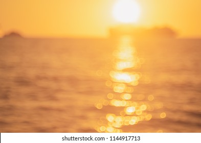 Blur tropical sunset beach with bokeh sun light wave abstract background. Copy space of outdoor summer vacation and travel adventure concept. Vintage tone filter color style.