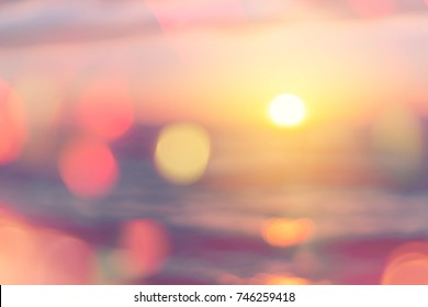 Blur tropical sunset beach with bokeh sun light wave sand abstract background. Copy space of outdoor summer vacation and travel adventure concept. Vintage tone filter color style.