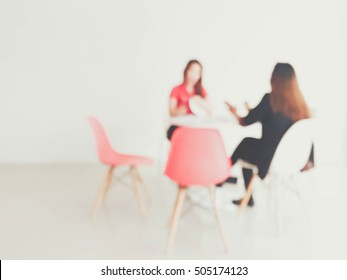 blur of two women talking in modern office : for background use