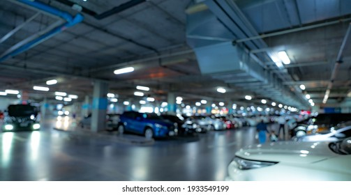 Blur underground car parking lot of shopping mall with opened light. Blur car driving and people walking inside of basement parking garage. Crowded car parked at underground modern car parking lot.